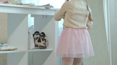 pigtailler : cheerful little girl with pigtails in a pink skirt tries on mothers shoes on heels and dances in front of a mirror, mothers wardrobe Stok Video