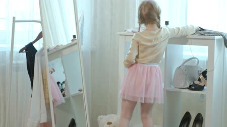 pigtailler : cheerful little girl with pigtails in a pink skirt puts hair on her hair in front of a mirror, her mother wardrobe Stok Video