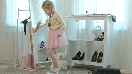 pigtailler : cheerful little girl with pigtails in a pink skirt tries on mothers shoes on heels and dances in front of a mirror with a bag, mothers wardrobe Stok Video