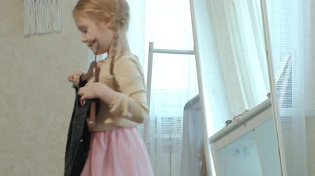 pigtailler : cheerful girl with pigtails in a pink skirt tries on adult mothers clothes, dresses, high heels and dances in front of a mirror with a bag, mothers wardrobe