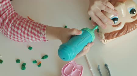 plastelíny : a young woman and a girl mold their teeth from plasticine, insert their teeth into a toy jaw, remove braces, play a dentist, mother and daughter,