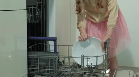 помощник : Cute blonde babe girl in a pink skirt, helps mom in the bright kitchen, loads plates, cups in the dishwasher Стоковые видеозаписи