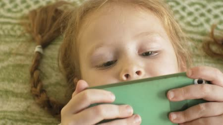 косички : happy girl child with blond hair and pigtails, lying on the sofa, using the phone, smiling, portrait Стоковые видеозаписи