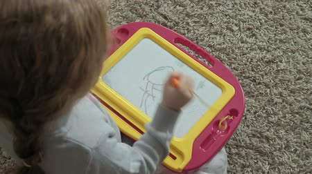 small pen : A little girl with red wavy hair lies on the floor and draws on a magnetic board. The concept of the educational process. close-up