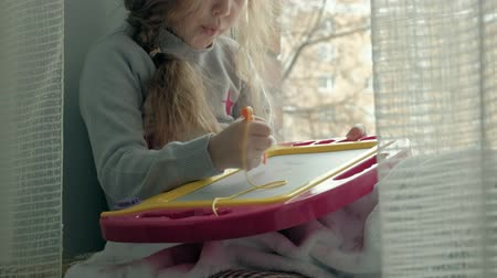 small pen : A little girl with red wavy hair sits on the windowsill and draws on a magnetic board. The concept of the educational process.