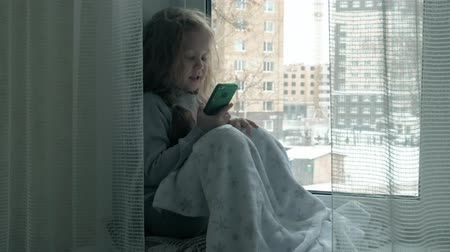 mobile game : happy little girl with wavy red hair sits on the windowsill, covering a blanket and using the phone, talking, video calling