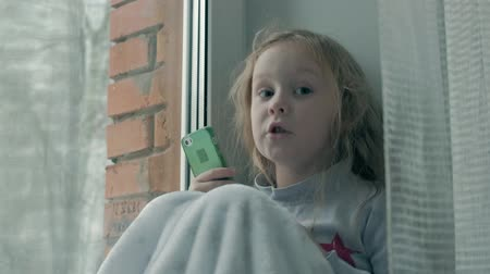 kapak : happy little girl with wavy red hair sitting on the windowsill, covering a blanket and using the phone, talking, video calling, close-up portrait Stok Video