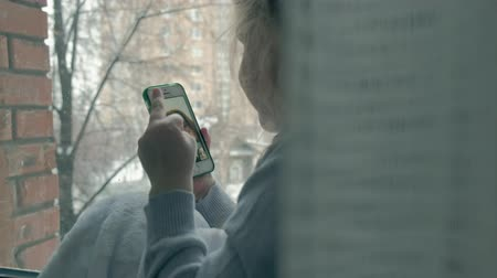 波打つ : happy little girl with wavy red hair sitting on the windowsill, covering a blanket and using the phone, talking, video calling, close-up portrait 動画素材