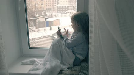oturur : happy little girl with wavy red hair sits on the windowsill, covering a blanket and using the phone, talking, video calling