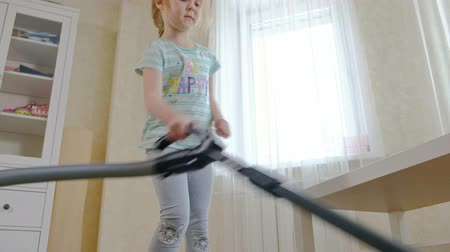 temizleme maddesi : a little girl with blond hair cleans up with a vacuum cleaner, brings order and cleanliness, helps mom Stok Video