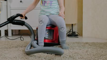 odkurzacz : a little girl with blond hair sits on a vacuum cleaner and cleans up, brings order and cleanliness, helps mom