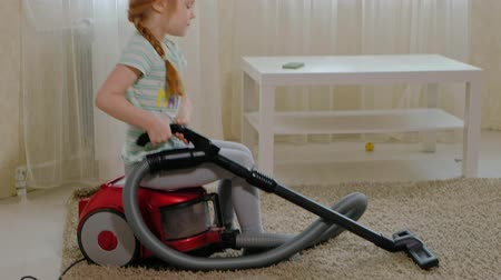 bonitinho : a little girl with blond hair sits on a vacuum cleaner and cleans up, brings order and cleanliness, helps mom