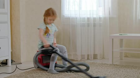 vácuo : a little girl with blond hair sits on a vacuum cleaner and cleans up, brings order and cleanliness, helps mom