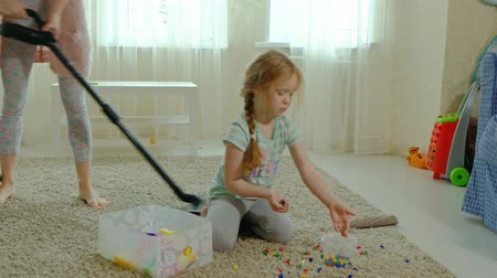 odkurzacz : mom and daughter, a young woman cleans up with a vacuum cleaner, a little girl with blond hair collects toys, the designer in a container, helps mom