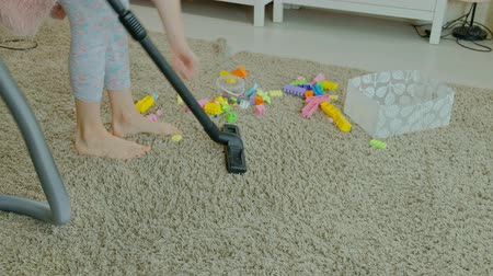собирают : mom and daughter, a young woman cleans up with a vacuum cleaner, a little girl with blond hair collects toys, the designer in a container, helps mom