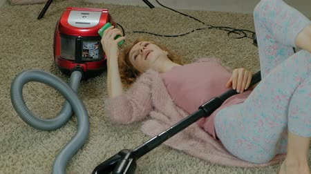 уборка : happy young woman or a housewife with a vacuum cleaner, lying on the floor, using the phone, having fun, playing, cleaning, household Стоковые видеозаписи