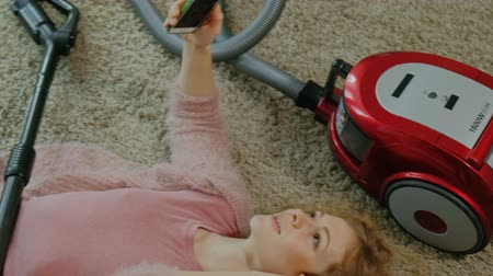 odkurzacz : happy young woman or housewife with a vacuum cleaner, lying on the half-headphones, uses the phone, listens to music, dances, cleaning, housekeeping