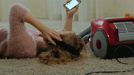 odkurzacz : happy young woman or housewife with a vacuum cleaner, lying on the half-headphones, uses the phone, listens to music, dances, cleaning, housekeeping, portriet
