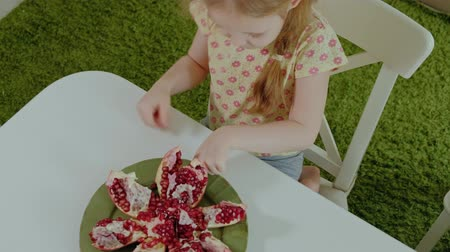roma : happy little girl with blond hair eats pomegranate, healthy food concept, close-up