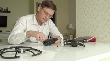 propeller toy : Mature man with glasses and a white shirt assembles a control panel for a quadrocopter, a concept for the study of technology
