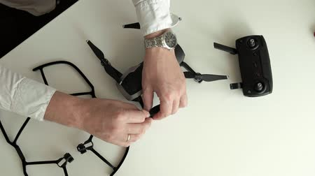 propeller toy : mature man with glasses and a white shirt assembles a quadrocopter, changes blades, the concept of learning techniques, top view Stock Footage