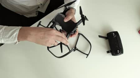 pervane : mature man with glasses and a white shirt assembles a quadrocopter, installs protection on the blades, the concept of studying technology, top view Stok Video
