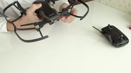 propeller toy : mature man with glasses and a white shirt assembles a quadrocopter, installs protection on the blades, the concept of studying technology, top view Stock Footage