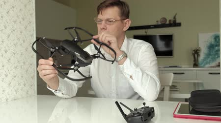 propeller toy : mature man with glasses and a white shirt collects a quadrocopter, examines it, the concept of studying technology