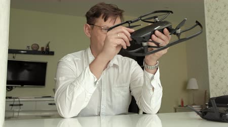 seçme : mature man with glasses and a white shirt collects a quadrocopter, examines it, the concept of studying technology