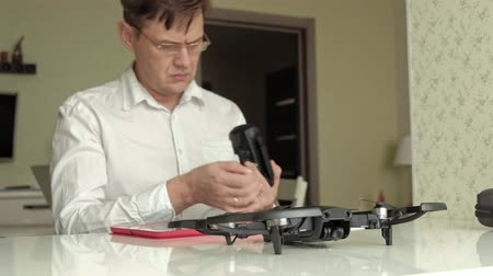 propeller toy : mature man in glasses and a white shirt assembles a quadrocopter, connects the controls, the concept of learning technology Stock Footage