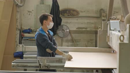 em branco : a man saws wooden door blanks on the machine, the production of village interior doors