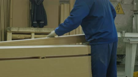 timber cutting : a man saws wooden door blanks on the machine, the production of village interior doors