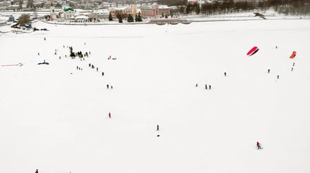 padák : CHEBOKSARY, RUSSIA - DECEMBER 31, 2018: Athletes involved in snowkiting, in the winter ride on the river in the costumes of Santa Claus, aerial photography from a quadrocopter Dostupné videozáznamy