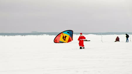 padák : CHEBOKSARY, RUSSIA - DECEMBER 31, 2018: snowkiting athletes ride on the river in Santa Claus costumes in winter