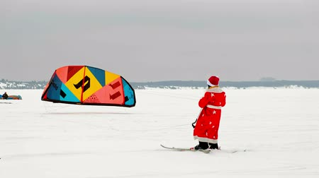 kiting : CHEBOKSARY, RUSSIA - DECEMBER 31, 2018: Snowkiting athlete, in the winter in a suit of Santa Clauss, lifts the parachute into the sky
