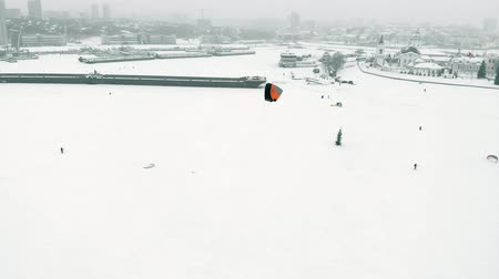 paraşüt : Snowkiting athletes ride on the river in Santa Claus costumes in winter