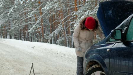 hood : woman with a straw car on the road in winter