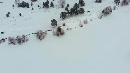 takes : Aerial top view of a frozen river among the snow. Aerial winter landscape. Copter shoot
