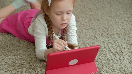 sitting floor : Little girl coloring on a tablet