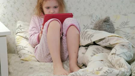 desgrenhado : little girl in bed playing on tablet