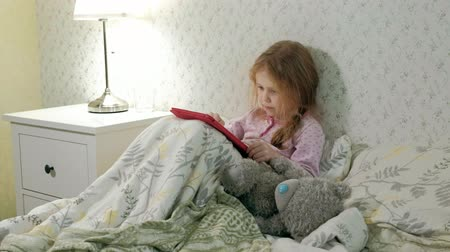 bastião : little girl in bed playing on tablet