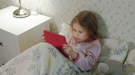 csak : little girl in bed playing on tablet