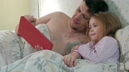 use computer : dad and little daughter on the bed playing on the tablet
