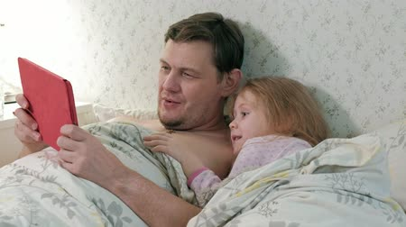 sen : dad and little daughter on the bed playing on the tablet