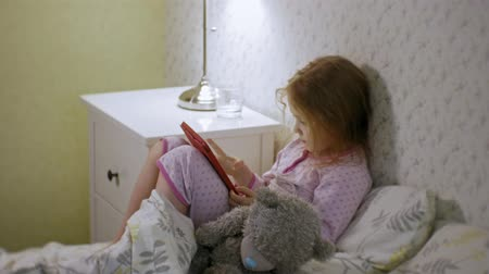 takes : little girl in bed playing on tablet
