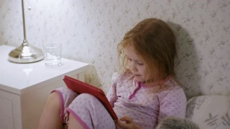 wakes : little girl in bed playing on tablet