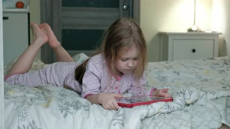 tabletler : little girl in bed playing on tablet