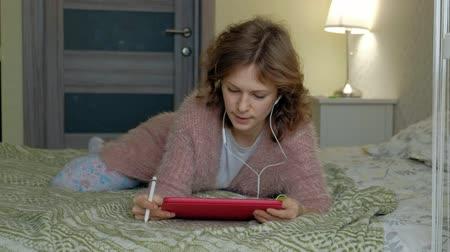 mesafe : Happy girl listening to music and draws with a stylus using a tablet in the bedroom at home. Web surfing, distance work conception, freelancer
