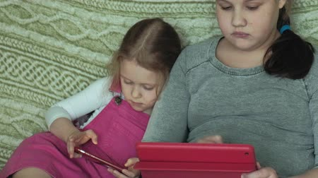 using stylus : girls sisters playing on the tablet in the room, web surfing, rest