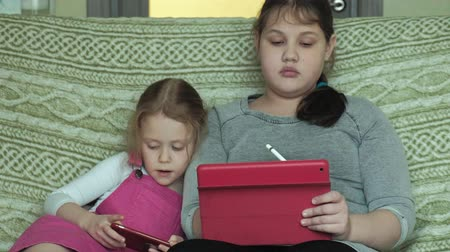 pré adolescente : girls sisters playing on the tablet in the room, web surfing, rest